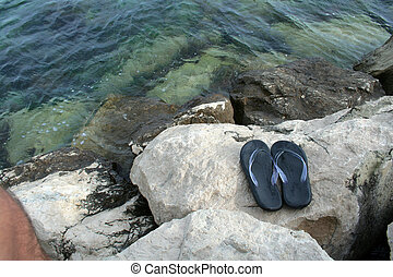 pair of sandals on the rocky coast in Croatia