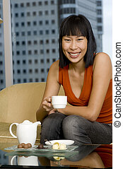 Woman Having Tea - A young smiling asian woman drinking tea...