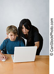 Adult assisting child on computer - An adult assists a child...