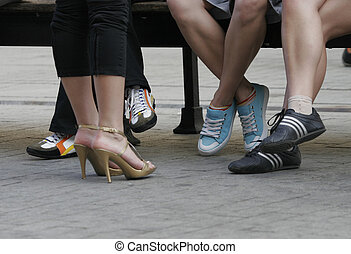 Four pairs female legs in different footwear