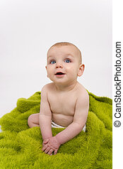 Blue Eyed in Green - A blue eyed baby sitting attentively on...