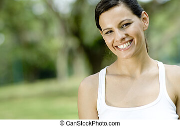 Outside - An attractive young woman standing in a park...
