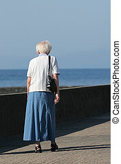 Old and Alone - Rear view of an elderly female walking alone...