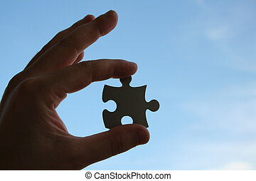 Finding - Human hand with jigsaw puzzle on blue sky...