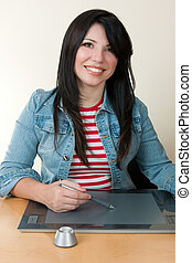 Woman using a graphic tablet and pen - A smiling woman...