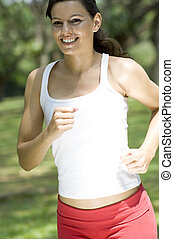 Female Fitness - A beautiful young woman running in the park