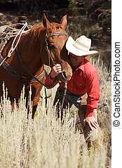 Cowboy and his horse - cowboy bending down and caring for...