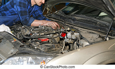mechanic working with engine in the car service