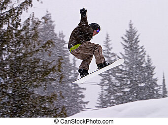 Jumping With A Snowboard - A man on a snowboard performing a...