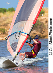 Man in wetsuit on fastmoving windsurfer - Fast moving...