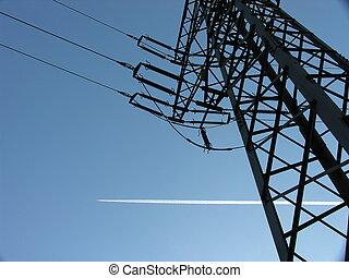 pylon electricity - a pylon with vapour trail against blue...