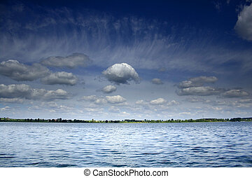 clouds over lake - white clouds on the blue sky over the...