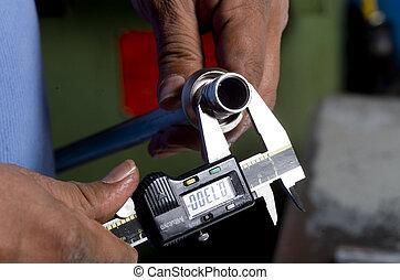 calliper in use - Image of a calliper measuring a pipe