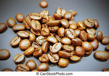 Coffee beans - pile of roasted coffee beans on a black...