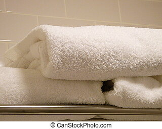 Plush Towels - A pile of folded plush towels in a bathroom