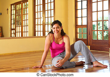 Healthy young woman in gym outfit sitting on the floor -...