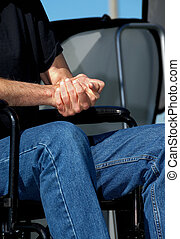Folded Hands in a Wheelchair - A man in a wheelchair sits...