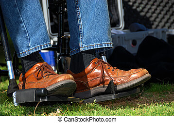 Feet in a Wheelchair - A mans feet in brown leather shoes as...