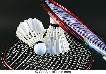 Badminton rackets and two shuttlecocks on a black background