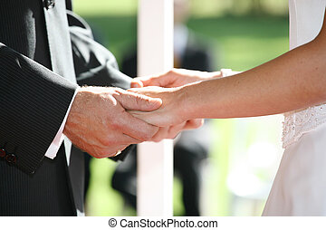 Holding Hands - A bride and groom holding hands at ceremony
