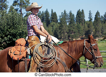 Smiling Cowgirl - cowgirl happy to be out riding her horse