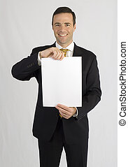 Handsome man in black suit holding up paper for viewing