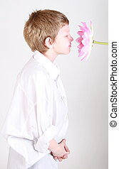 simple pleasures - Cute little boy smelling a big pink lily.