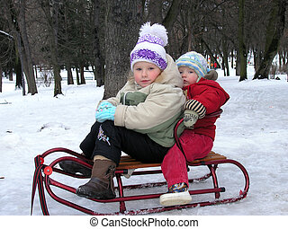childrens on sledge - Two childrens on sledge in winter park...