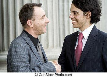 Business Deal - Two businessmen shaking hands outside in...