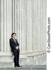 Businessman and Building - A young businessman leaning...