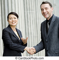 Happy Business Deal - Two business people smiling and...