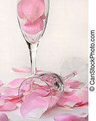 petals and flutes - two wine glasses - one tipped filled and...