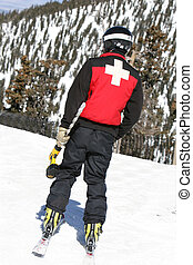 A ski patrol member carries a large drill to setup warning...