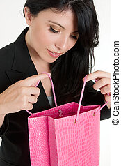 Woman opening up a gift bag - A woman peers into a colourful...