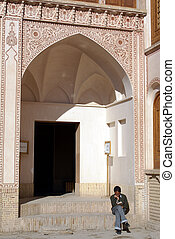 Yong man with book - Man on the steps of building in Kashan,...