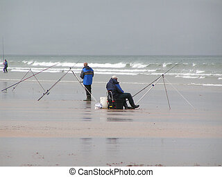 Sea fishing - People sea fishing on the shore on a drizzly...