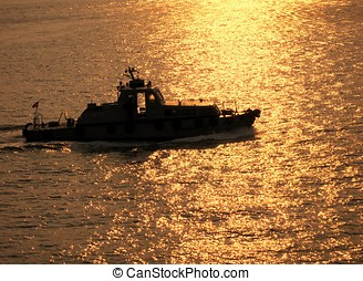 Coastguard Vessel - -- crossing the sea during sunset time