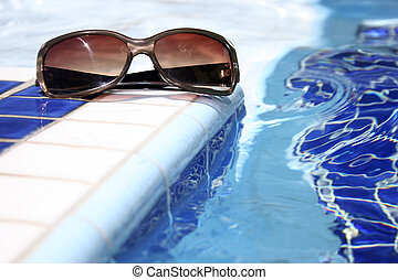 Pool Sunglasses - Sunglasses by bright swimming pool with...