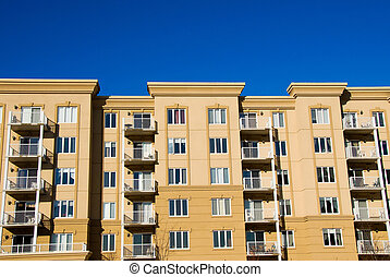 Condos - modern beige and brown apartment condos on blue sky