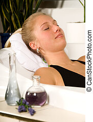 Happy girl - blond woman in a spa bath relaxing with oils