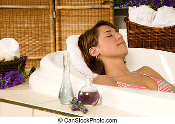 Aromatherapy - brunette girl in a spa bath relaxing