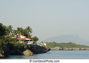 house over the sea - house on cliff over the sea with island...