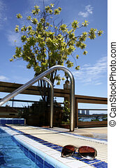 Pool Sunglasses - Sunglasses by swimming pool with foliage...