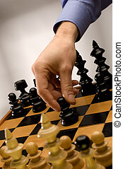 chess - hand moving black chess figure close up