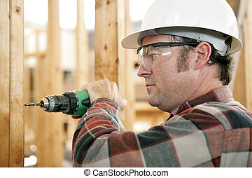 Safety On The Job - A construction worker drilling and...