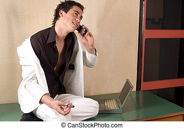 Talking on the phone - Young adult man sitting on desk,...