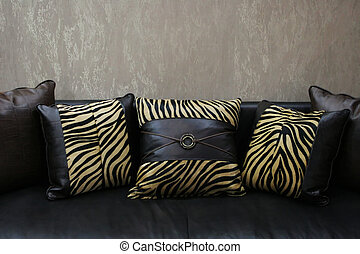 Modern couch with leather leopard skin cushions (copy space)...