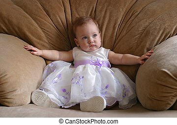 Small princess - The little girl in a beautiful dress sits...