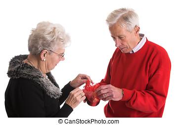 Elderly couple giving presents