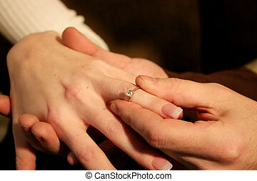 Engagement ring - A man is slipping an engagement ring onto...
